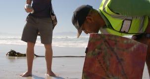 Manliga volontärer som gör ren stranden på en solig dag 4k stock video