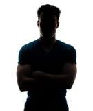 Manlign figurerar i silhouetten som ser kameran Arkivfoto