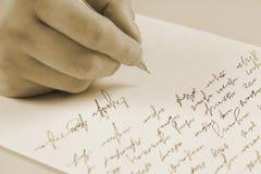Manlign räcker handstil på ett pappers- Arkivbild