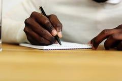 Manlign räcker handstil på ett pappers- Royaltyfri Fotografi