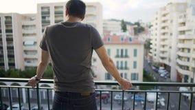 Manligt anseende på balkong och tycka omsikt på gatan efter arbetsam dag arkivfilmer