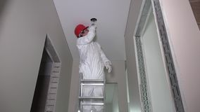 Manligt arbetaranseende på stege- och klipphålet i korridortak lager videofilmer