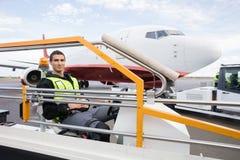 Manligt arbetarsammanträde på bagagetransportörlastbilen Arkivbild