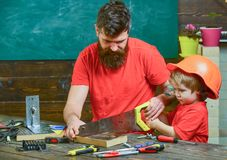Manligt arbetsuppgiftbegrepp Avla föräldern med skägget som undervisar den lilla sonen till att såga med den skarpa handsawen, sn arkivfoto