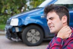 Manligt bilistlidande från pisksnärt efter bilolycka royaltyfri bild