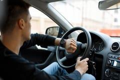 Manligt chaufförsammanträde i bil, i trafikstockning och att se klockan arkivfoto