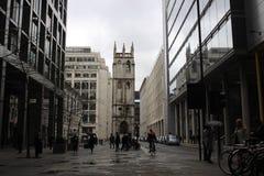 Manligt cykelpendlare och folk i gatan i stad av London, England, grå modern arkitektur Royaltyfri Bild