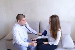 Manligt doktorsmåtttryck av den kvinnliga patienten med tonometer w royaltyfria foton