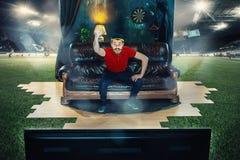 Manligt fansammanträde på soffan och den hållande ögonen på TV:N i mitt av ett fotbollfält Arkivfoto