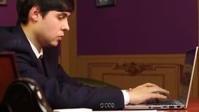 Manligt framstickande som i regeringsställning sitter och att arbeta på datoren, arbetsdags stock video