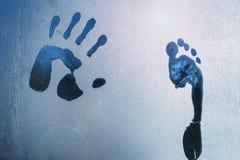 Manligt hand- och fottryck på djupfryst fönsterexponeringsglas royaltyfria bilder
