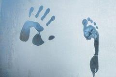 Manligt hand- och fottryck på djupfryst fönsterexponeringsglas royaltyfri bild