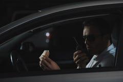 manligt hemligt medel i solglasögon som har lunch och använder talkiewalkie arkivfoton