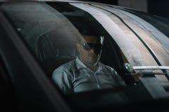 manligt hemligt medel i solglasögon som sitter i bil med papperskoppen kaffe, medan göra arkivfoton