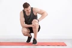 Manligt idrottsman nenlidande från knä smärtar inomhus royaltyfri fotografi