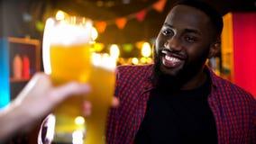 Manligt klirra ölexponeringsglas för gladlynt afrikansk amerikan som tycker om resultattid i stång fotografering för bildbyråer