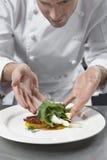 Manligt kockPreparing Salad In kök fotografering för bildbyråer
