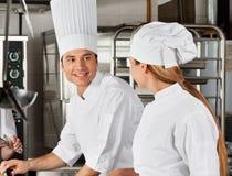 Manligt kockWith Colleague At kök Fotografering för Bildbyråer