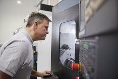 Manligt maskineri för teknikerWatching Progress Of CNC i fabrik fotografering för bildbyråer