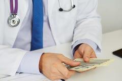 Manligt medicindoktorsinnehav i handgruppen av hundra dollar b royaltyfri fotografi