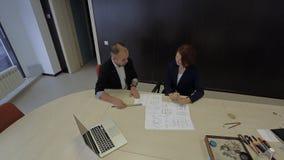 Manligt och kvinnligt arbete tillsammans på en ritning arkivfilmer