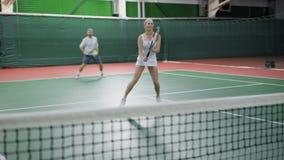 Manligt och kvinnligt tennislag som spelar matchen på domstolen stock video