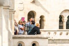 Manligt och kvinnligt turist- anseende på en synvinkel utanför och nedanför Matthias Church i Budapest Royaltyfria Foton