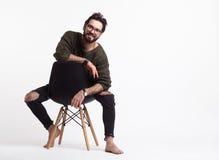 Manligt posera för Hipster på stol Royaltyfri Bild