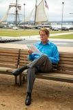 Manligt sammanträde på en bänk som läser ett dokument royaltyfria bilder