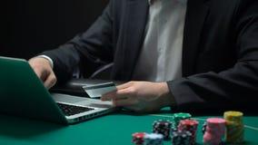 Manligt skrivande in kortnummer på bärbar datorapplikationen, chiper på tabellen, online-dobbleri arkivfilmer
