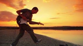 Manligt spela för gitarrist vaggar och att hoppa i lager videofilmer