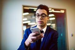 Manligt stolt framstickandeläsningmeddelande på mobiltelefonen Advokat i dräkt som skriver text på celltelefonen royaltyfri bild