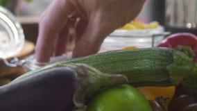 Manligt ta för hand saltar för att salta mat, medan laga mat vegetarisk sallad på kök Att ta för kockkockhand saltar för stock video