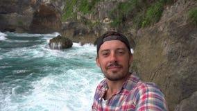 Manligt tagande selfiefoto nära härligt landskap, havvågor lager videofilmer