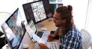 Manligt utövande arbete över bärbara datorn och den grafiska minnestavlan på hans skrivbord 4k lager videofilmer