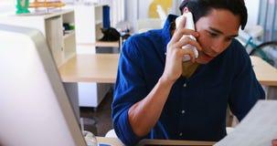 Manligt utövande samtal på mobiltelefonen, medan arbeta på hans skrivbord 4k lager videofilmer