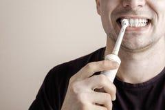 Manlokalvårdtänder med den elektriska tandborsten Royaltyfria Foton