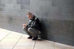 Manlooking an seinem Handy Stockfoto