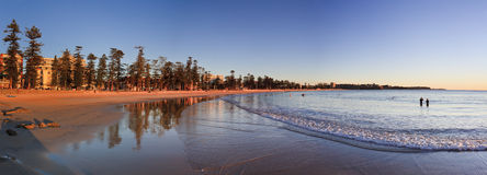 Manly Beach Rise 02 Pan. Australia NSW Manly beach and waterfront at sunrise panoramic view on wide sand and surfing and swimming people Royalty Free Stock Images