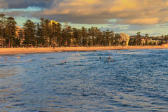 Manly Beach Sydney Australia. Early morning swimmers at Manly beach with people also walking along sand Stock Photography