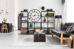 Manly flat with round clock. Laptop on black table and wooden dark sofa in manly flat interior with round clock on the wall and stools at kitchen island Stock Photos