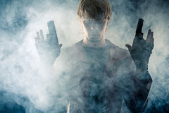 Manly hero with pistols in hands. In the smoke Royalty Free Stock Image