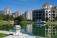 Condos on a Manmade Lagoon. Lone boat sits on still, refective waters of man-made lagoon in front of vacation rental condos and hotel set against brilliant blue Royalty Free Stock Photography