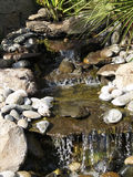 Manmade rock waterfall fountain pond outdoors moss Royalty Free Stock Image