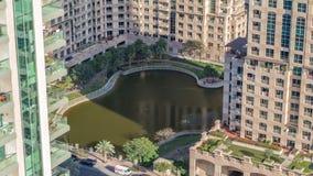 Manmade sjö och bostads- byggnader i gräsplanneighbourhoodtimelapse i Dubai, UAE lager videofilmer