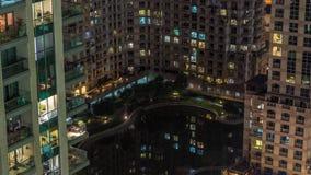 Manmade sjö och bostads- byggnader i timelapse för gräsplanneighbourhoodnatt i Dubai, UAE arkivfilmer