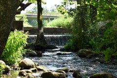 Manmade vattenfall på floden under bron Royaltyfri Foto