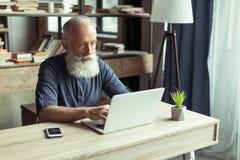 Manmaskinskrivning på hemmastadd kontorsarbetsplats för bärbar dator Fotografering för Bildbyråer