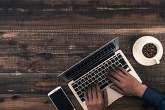 Manmaskinskrivningbärbar dator på träskrivbordet Arkivbild