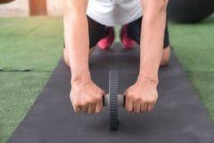 Mannübungsunterleib mit einer AB-Rolle Stockfotos